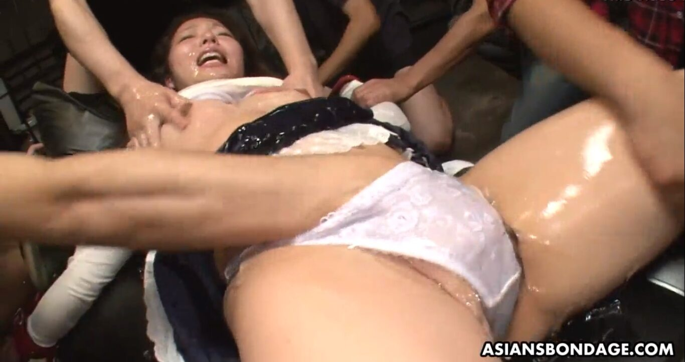 All the bondage masters who participated in this BDSM video, started to spread the oil all over the Asian whore's body